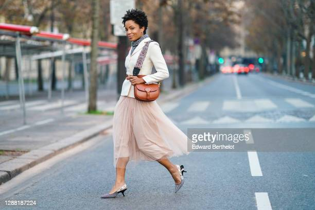 Ellie Delphine wears a full Dior look made of a gray wool turtleneck pullover, a white double breasted blazer jacket, a brown leather Dior bag, a...