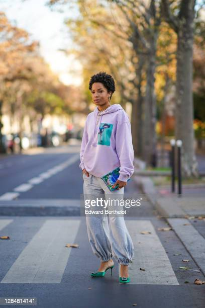 Ellie Delphine wears a mauve pale purple hoodie sweater with a printed green patch depicting a hand and a dog from Acne Studios gray sportswear pants...