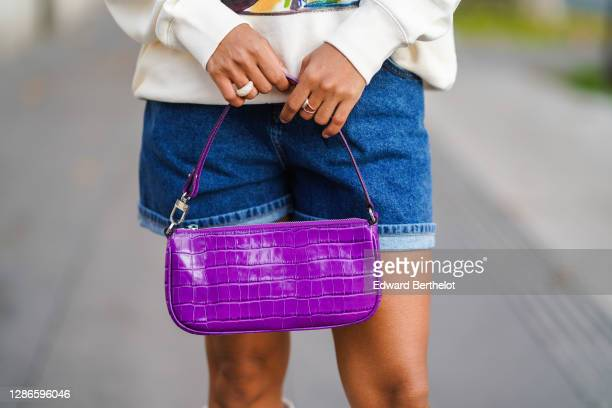 Ellie Delphine wears Asos blue denim shorts, a purple leather crocodile pattern bag from Far, on November 19, 2020 in Paris, France.