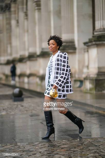 Ellie Delphine wears earrings, a necklace, a full look from 404 Studio made of a black and white checked jacket with embroidery, a t-shirt with...