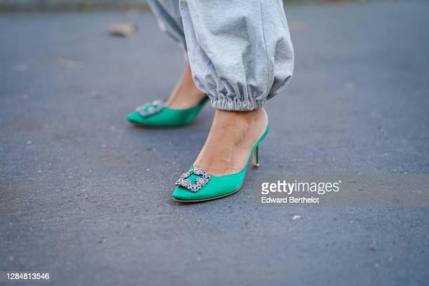 Ellie Delphine wears gray sportswear pants from Norma Kamali, green pointy bejeweled shoes from Manolo Blahnik, on November 05, 2020 in Paris, France.