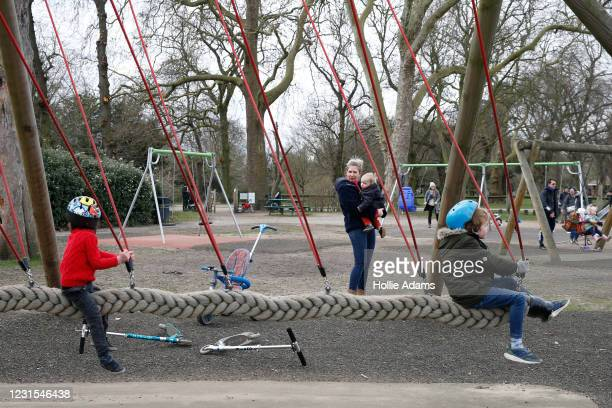 Ellie Martin-Sperry holds Sebastian Wilson while watching watching her son Dominic Wilson and Freddie play on a swing at the Victoria Park playground...