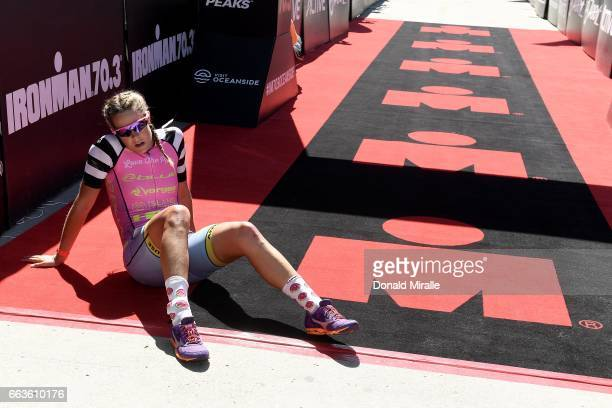 Ellie Salthouse of Australia falls exhausted at the finish line after finishing 2nd during the IRONMAN 703 Oceanside on April 1 2017 in Oceanside...
