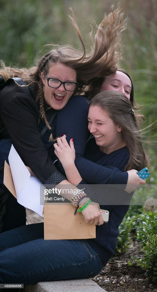 Ellie Wood, who got two grade A's and a A* and is taking a place at Cambridge is congratulated by her friends Melissa Fox-Robinson and Clare Hemmings as she opens her A-level results at Yate International Academy on August 14, 2014 in Bristol, England. Across England and Wales students were receiving their A-level results this morning and for the first time in over 30 years there has been a slight fall in the pass rate. However, there is now a record number of university places available and some students may still get their places even if they did not get the grades.