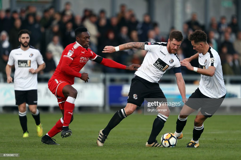 Elliot Bradbrook of Dartford is tackled by Amine Linganzi of Swindon Town during The Emirates FA Cup first round match between Dartford and Swindon Town at the Princes Park Stadium on November 5, 2017 in Dartford, England.