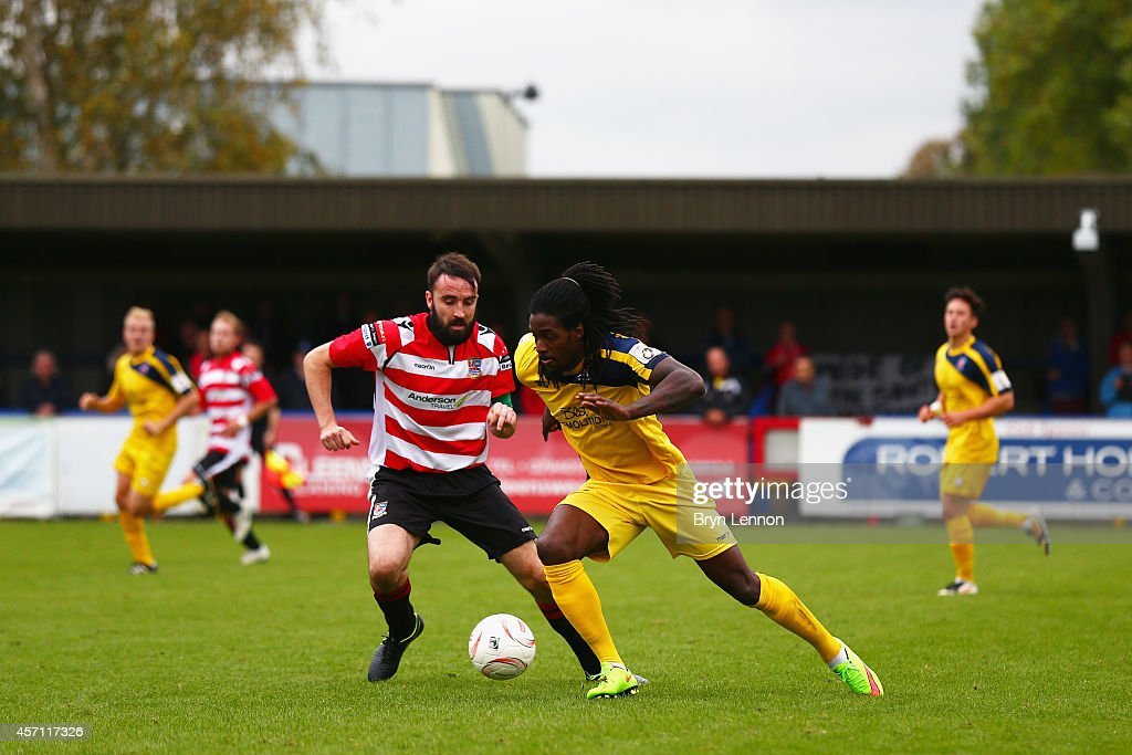 Elliot Charles of Eastbourne Borough is tackled by Alan Inns of Kingstonian during the FA Cup Qualifying Third Round match between Kingstonian and Eastbourne Borough at The Cherry Red Records Stadium on October 12, 2014 in Kingston upon Thames, England.
