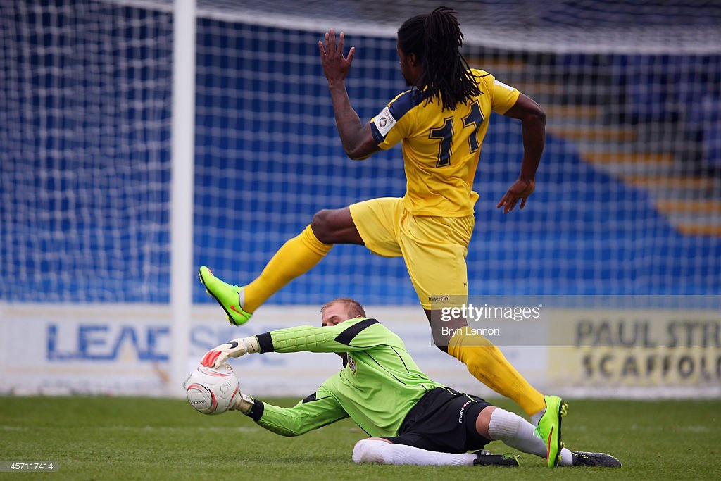 Elliot Charles of Eastbourne Borough steps over Rob Tolfrey of Kingstonian during the FA Cup Qualifying Third Round match between Kingstonian and Eastbourne Borough at The Cherry Red Records Stadium on October 12, 2014 in Kingston upon Thames, England.