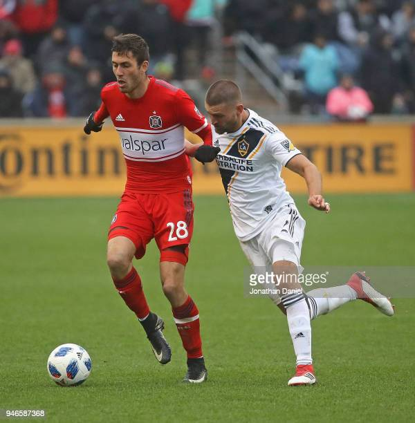 Elliot Collier of the Chicago Fire is pressured by Perry Kitchen of Los Angeles Galaxy at Toyota Park on April 14 2018 in Bridgeview Illinois The...