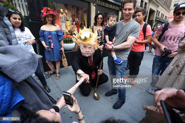 Elliot Crown wears a Donald Trump headpiece during the Easter Parade on Fifth Avenue on April 16 2017 in New York City USA