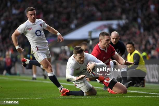 Elliot Daly of England goes past George North of Wales to score his sides second try during the 2020 Guinness Six Nations match between England and...