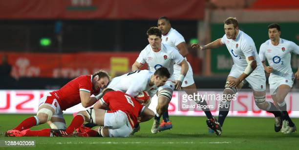 Elliot Daly of England is tackled by Alun Wyn Jones and Shane Lewis-Hughes during the Quilter International match between Wales and England as part...