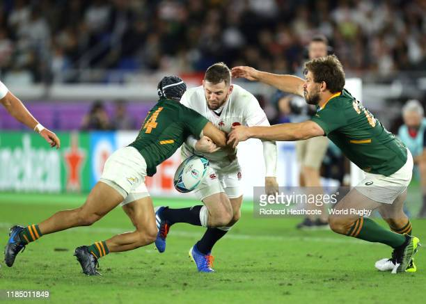 Elliot Daly of England is tackled by Cheslin Kolbe and Frans Steyn of South Africa during the Rugby World Cup 2019 Final between England and South...