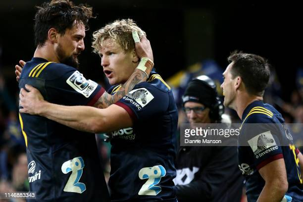 Elliot Dixon of the Highlanders congratulates teammate James Lentjes after he scores a try during the Round 12 Super Rugby match between the...