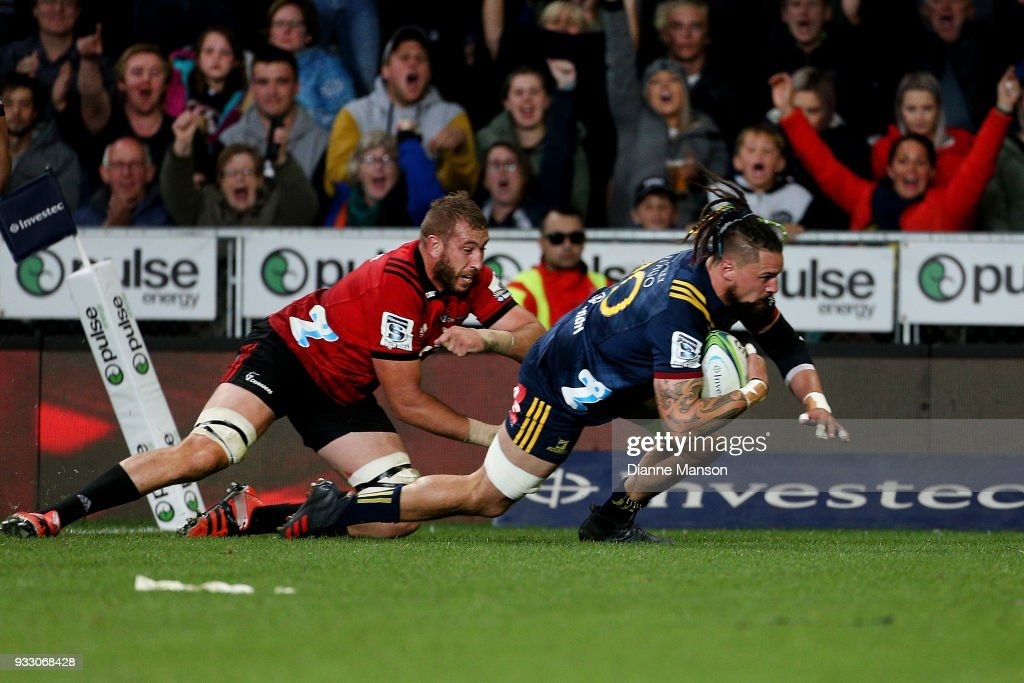 Elliot Dixon of the Highlanders dives over to score a try in the tackle of Luke Romano of the Crusaders during the round five Super Rugby match between the Highlanders and the Crusaders at Forsyth Barr Stadium on March 17, 2018 in Dunedin, New Zealand.