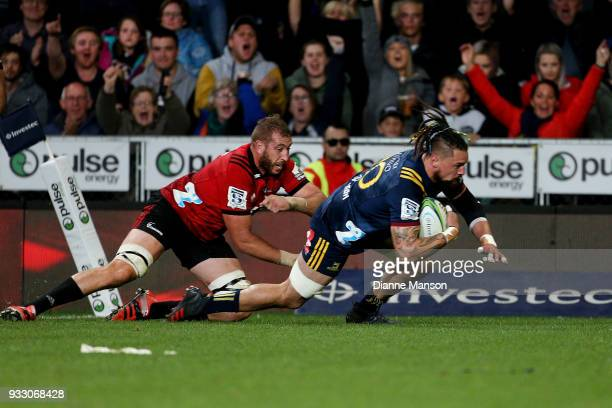 Elliot Dixon of the Highlanders dives over to score a try in the tackle of Luke Romano of the Crusaders during the round five Super Rugby match...