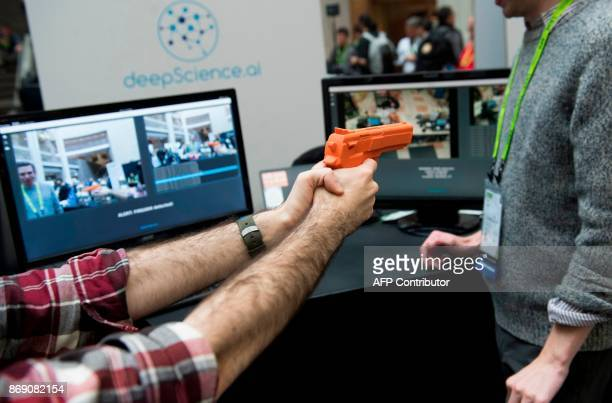 Elliot Hirsch of Deep Science holds a fake gun as he demonstrates the company's security system to automatically detect firearms and thieves to be...