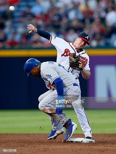Elliot Johnson of the Atlanta Braves turns a double play as Carl Crawford of the Los Angeles Dodgers slides into second in the third inning during...