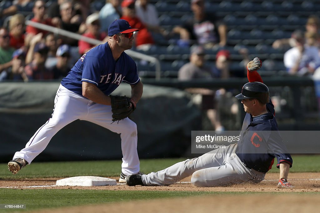 Elliot Johnson #30 of the Cleveland Indians slides into third base with a triple in the top of the sixth inning against the Texas Rangers at Surprise Stadium on March 03, 2014 in Surprise, Arizona.