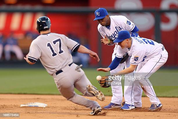 Elliot Johnson of the Kansas City Royals and Alcides Escobar try to field a ball hit by Lyle Overbay of the New York Yankees as Jayson Nix advances...