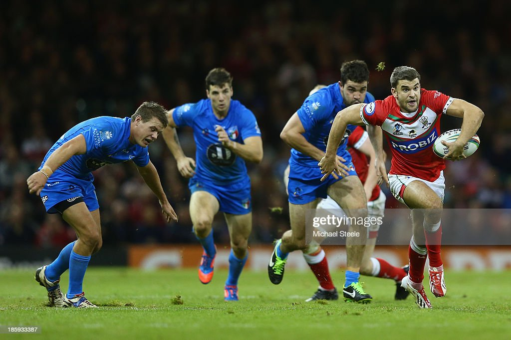 Elliot Kear (R) of Wales breaks clear of Ryan Ghietti (L) and Chris Centrone of Italy on his way to setting up the second try during the Rugby League World Cup Inter group match between Wales and Italy at the Millennium Stadium on October 26, 2013 in Cardiff, Wales.