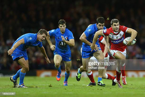 Elliot Kear of Wales breaks clear of Ryan Ghietti and Chris Centrone of Italy on his way to setting up the second try during the Rugby League World...