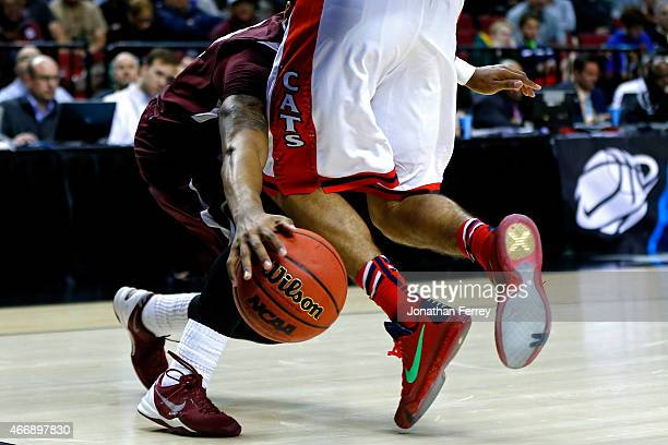 Elliott Pitts of the Arizona Wildcats defends Madarious Gibbs of the Texas Southern Tigers in the second half during the second round of the 2015...