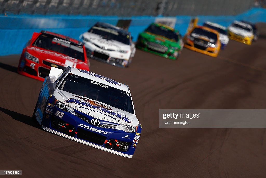 Elliott Sadler, driver of the #55 Aaron's Dream Machine Toyota, leads a pack of cars during the NASCAR Sprint Cup Series AdvoCare 500 at Phoenix International Raceway on November 10, 2013 in Avondale, Arizona.