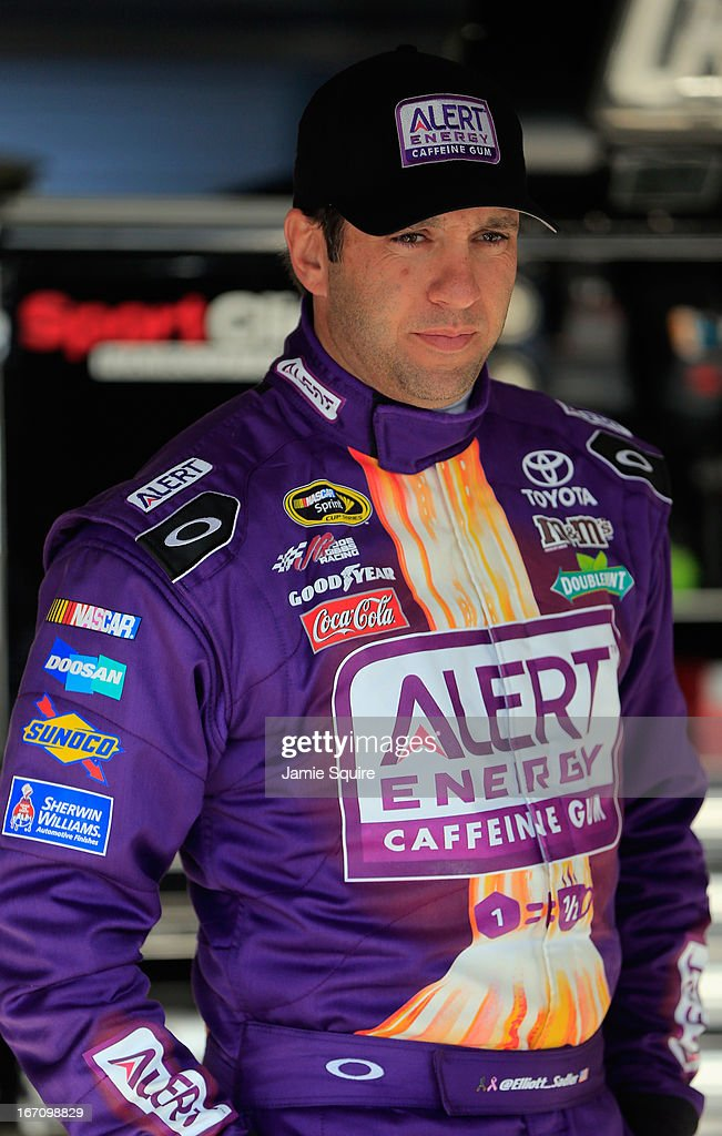 Elliott Sadler, driver of the #81 ALERT Energy Gum Toyota, stands in the garage area during practice for the NASCAR Sprint Cup Series STP 400 at Kansas Speedway on April 20, 2013 in Kansas City, Kansas.
