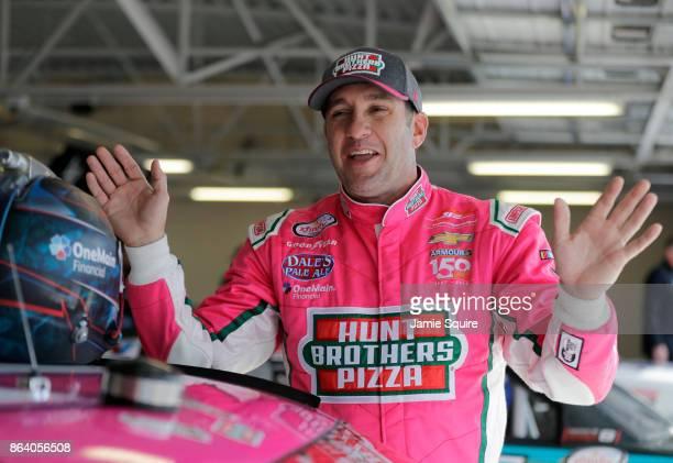 Elliott Sadler driver of the Hunt Brothers Pizza Chevrolet speaks to Daniel Hemric driver of the Blue Gate Bank Chevrolet in the garage during...