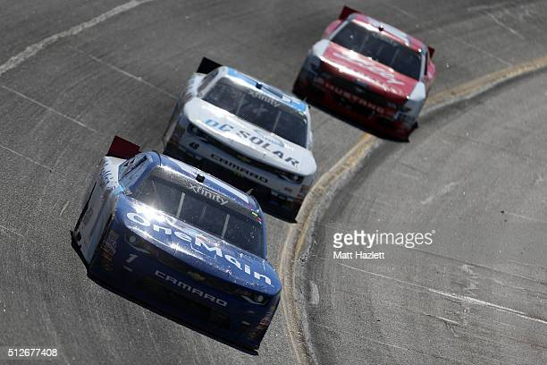 Elliott Sadler driver of the OneMain Chevrolet leads Brennan Poole driver of the DC Solar Chevrolet and Ryan Reed driver of the Lilly...