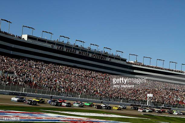 Elliott Sadler driver of the OneMain Financial Chevrolet and Kasey Kahne driver of the Great Clips Chevrolet lead the field during the NASCAR...