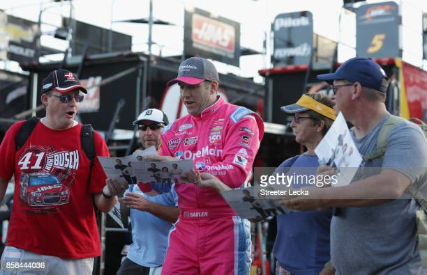Elliott Sadler driver of the OneMain Financial Chevrolet signs autographs for fans during practice for the NASCAR XFINITY Series Drive for the Cure...