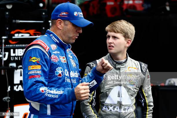 Elliott Sadler driver of the OneMain Financial Chevrolet talks with William Byron driver of the AXALTA/Progressive Powder Coating Inc Chev during...