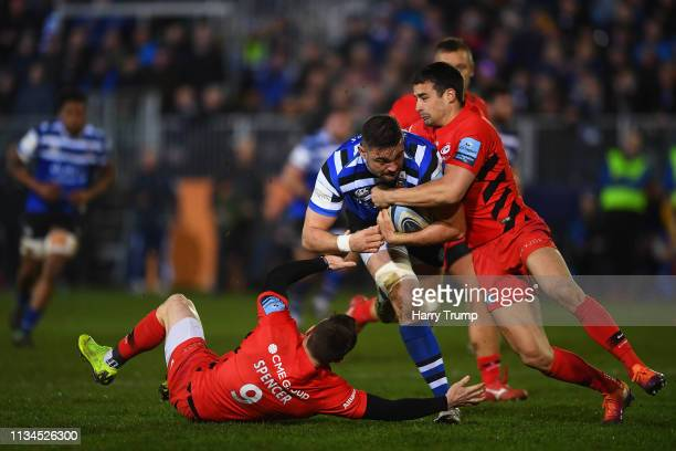Elliott Stooke of Bath is tackled by Ben Spencer and Alex Lozowski of Saracens during the Gallagher Premiership Rugby match between Bath Rugby and...