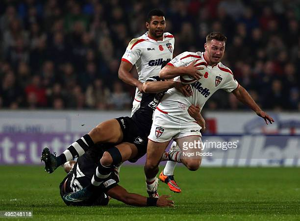 Elliott Whoitehead of England tackled by Adam Blair and Jordan Kahu of New Zealand during the International Rugby League Test Series match between...