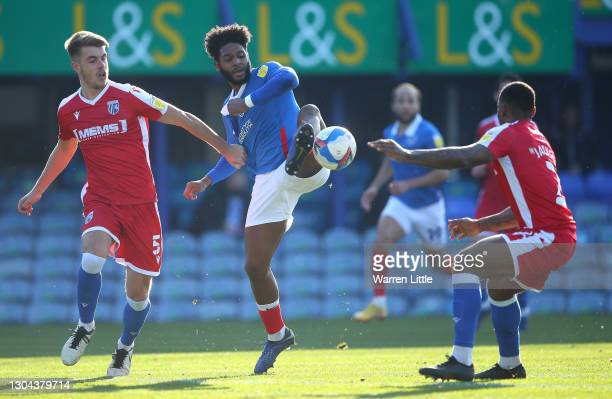 Ellis Harrison of Portsmouth FC is tackled by Jack Tucker and Ryan Jackson of Gillingham FC during the Sky Bet League One match between Portsmouth...