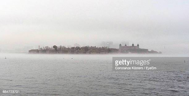ellis island on sea during foggy weather - ellis island stock pictures, royalty-free photos & images