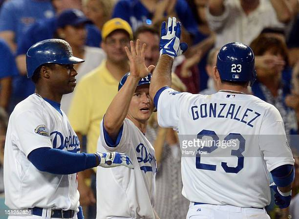 J Ellis of the Los Angeles Dodgers celebrates his run from an Adrian Gonzalez sacrifice fly with Hanley Ramirez for a 31 lead over the San Diego...