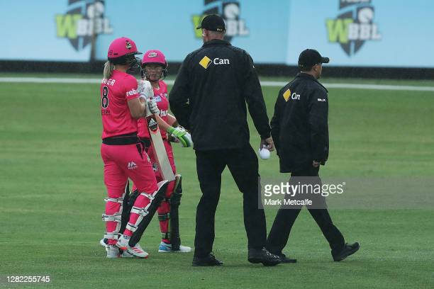Ellyse Perry and Alyssa Healy of the Sixers talk to the match umpires as they walk from the field for a rain delay during the Women's Big Bash League...