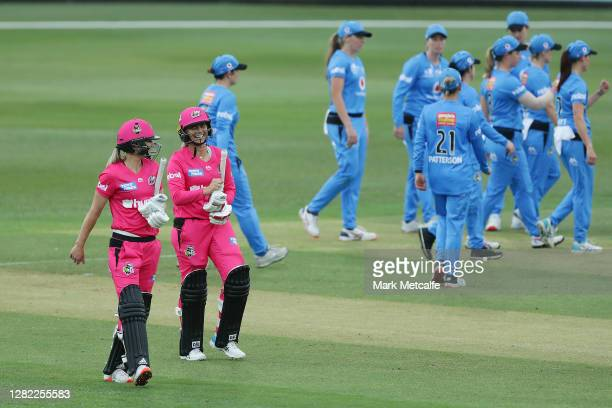 Ellyse Perry and Ashleigh Gardner of the Sixers smile as they walk off after victory during the Women's Big Bash League WBBL match between the Sydney...