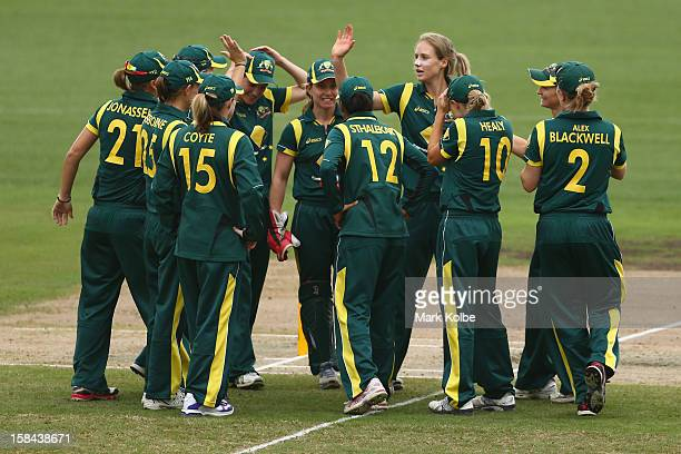 Ellyse Perry of Australia celebrates with her team after taking the wicket of Suzie Bates of New Zealand during game three of the One Day...
