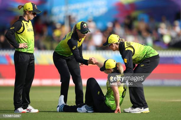 Ellyse Perry of Australia is assisted up by teammates during the ICC Women's T20 Cricket World Cup match between Australia and New Zealand at...
