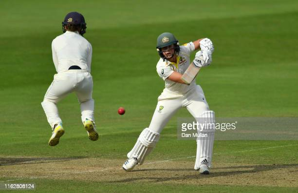 Ellyse Perry of Australia plays a shot past Fran Wilson of England during the Kia Women's Test Match between England Women and Australia Women at The...