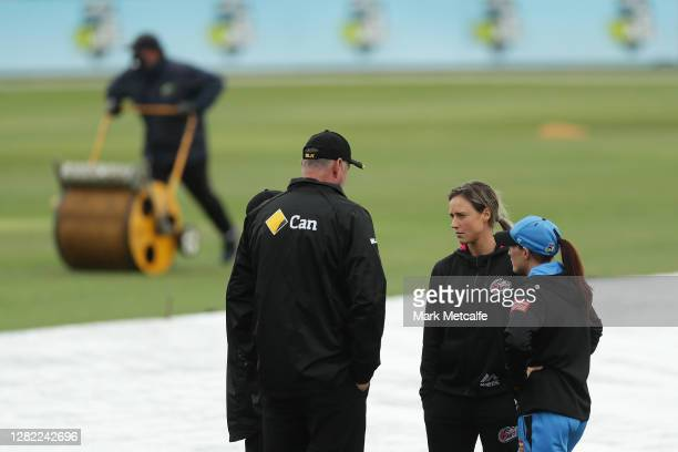Ellyse Perry of the Sixers and Megan Schutt of the Strikers speak to the match officials during the Women's Big Bash League WBBL match between the...