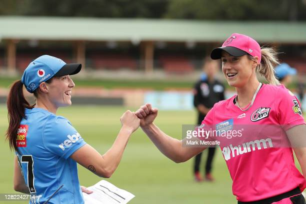 Ellyse Perry of the Sixers and Megan Schutt of the Strikers take part in the bat toss during the Women's Big Bash League WBBL match between the...