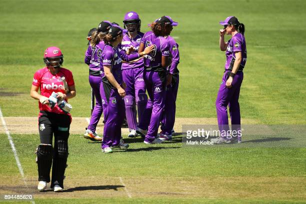 Ellyse Perry of the Sixers looks dejected as the Hurricanes celebrate her run out during the Women's Big Bash League match between the Hobart...