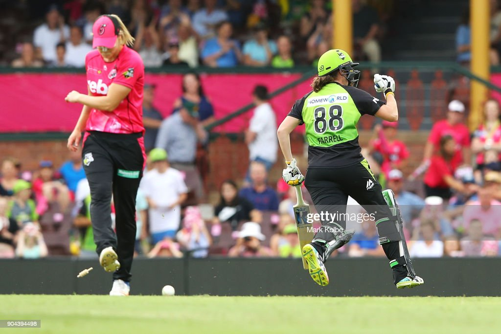 Ellyse Perry of the Sixers shows her frustration as Rene Farrell of the Thunder celebrates victory during the Women's Big Bash League match between the Sydney Sixers and the Sydney Thunder at Sydney Cricket Ground on January 13, 2018 in Sydney, Australia.
