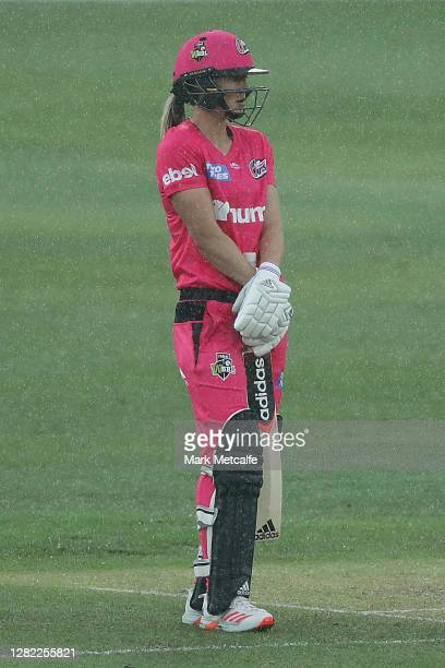 Ellyse Perry of the Sixers stands in the rain before the umpire called for a rain delay during the Women's Big Bash League WBBL match between the...