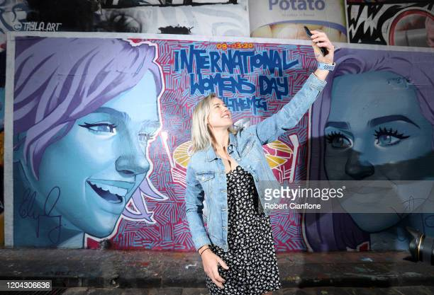 Ellyse Perry takes a selfie in front of an ICC T20 World Cup mural painted by local artist Tayla Broekman during an Australian Women's T20 media...