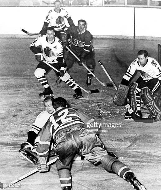 Elmer Vasko of the Chicago Blackhawks tries to block the shot of Dickie Moore of the Montreal Canadiens as goalie Glenn Hall Pierre Pilot and Murray...